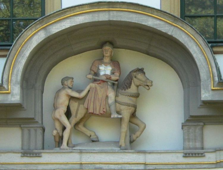 """St. Martin statue at the gate of Hochst Castle in Germany. Legend says that Martin, a soldier, found a naked beggar asking for alms in the name of Christ. The soldier cut his military cloak in two and gave him half. The next night Jesus, wearing half a cloak, appeared to Martin and said, """"Martin, a simple catechumen, covered me with this garment."""""""