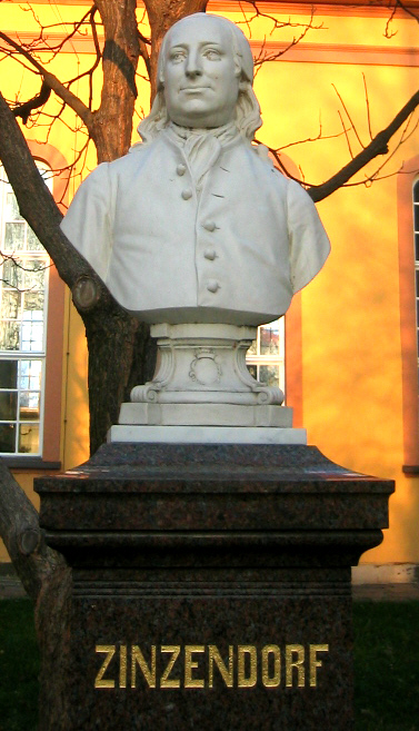 """Count Nicolaus von Zinzendorf developed a personal """"theology of the heart,"""" which led him to shelter Czech Protestants of the Unitas Fratrum (Bohemian Brethren, Moravians). They developed a rich liturgical and devotional life, for which he wrote many hymns, and a zeal for missionary activity. In the Pennsylvania colony (USA) he tried to bring together many denominations in unity. This monument stands in Herrnhut, Germany, the Moravian village on his estate."""