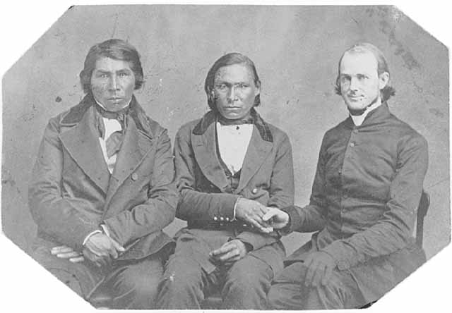 """Enmegahbowh, left, with colleagues Isaac Manitowob and James Lloyd Breck, """"the Apostle of the Wilderness"""" and founder of two extant seminaries. Enmegahbowh, an Ottawa Indian from Canada, was a peacemaker and the first Native American priest in the Episcopal Church. (Minnesota Historical Society, 1865)"""