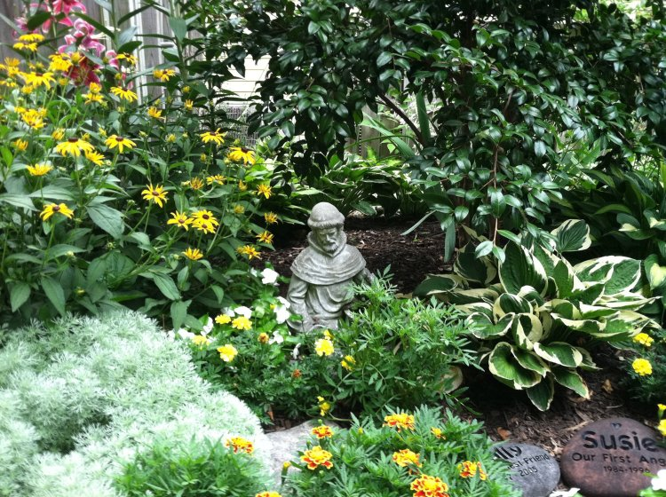 St. Francis statue watches over a flower garden in Maryland, where two beloved pets are buried. (William Thomas)