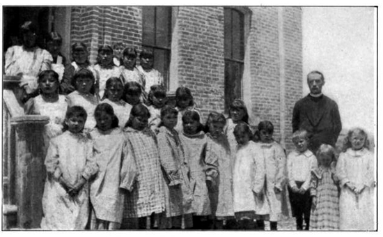 John Roberts was a priest and missionary among the Shoshone and Arapahoe Indians in Wyoming. He worked tirelessly establishing schools and churches from his arrival in 1883 to his death in 1949. Above in 1906, with students at his Fort Washakie Mission School for girls, which complemented a nearby government school for boys.