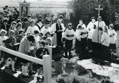 Rogation Day, 1967: The rector, parishioners and brass band of St. Michael's, Bunwell, England, walk the parish boundaries and pause to bless a stream. This is pure nostalgia now, but public processions remain a valuable tool. (Bunwell Heritage Group)