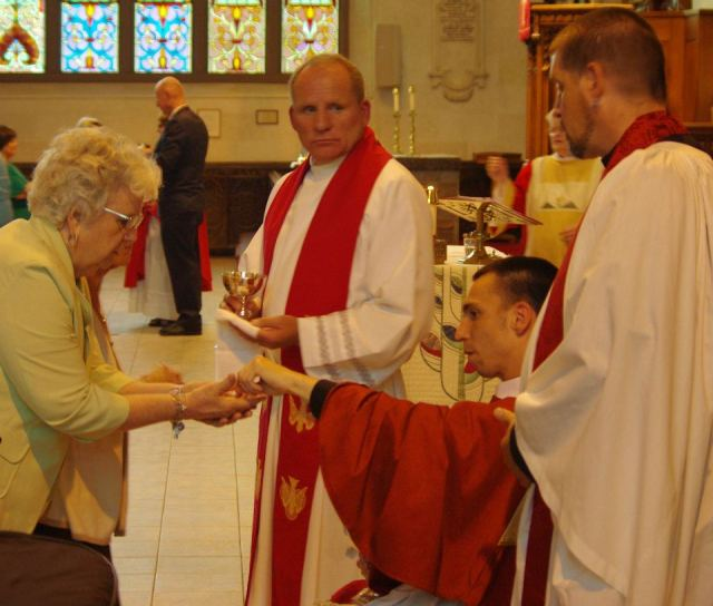 Fr. Matthew Arguin, a priest of the Anglican Church of Canada, distributing the bread of life.