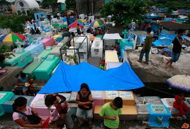 """All Saints' Day at a cemetery in suburban Manila, 2010, where Filipinos' custom is """"to remember their dead, clean the graves, and decorate them with flowers. While the purpose is somber, the effect is a picnic, full of merrymaking and laughter. Everyone goes to the cemetery, and some even stay overnight."""" (Text by Karen A. de la Trinidad)"""