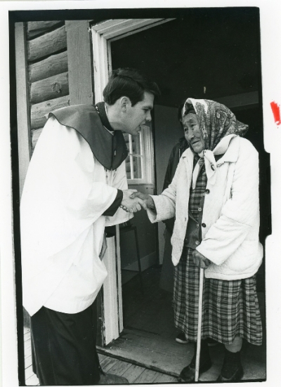 Tom Tull greeting one of the parish grandmothers after Sunday Morning Prayer in Fort Yukon, Alaska, about 1973. After training the last class of American Church Army evangelists, including me, he ended up in San Francisco and became an AIDS activist within the Church. But he didn't leave his heart in San Francisco; he left his heart in Fort Yukon. He would love to see the enormous growth of local and foreign mission work in today's Episcopal Church. (Ed Eckstein)
