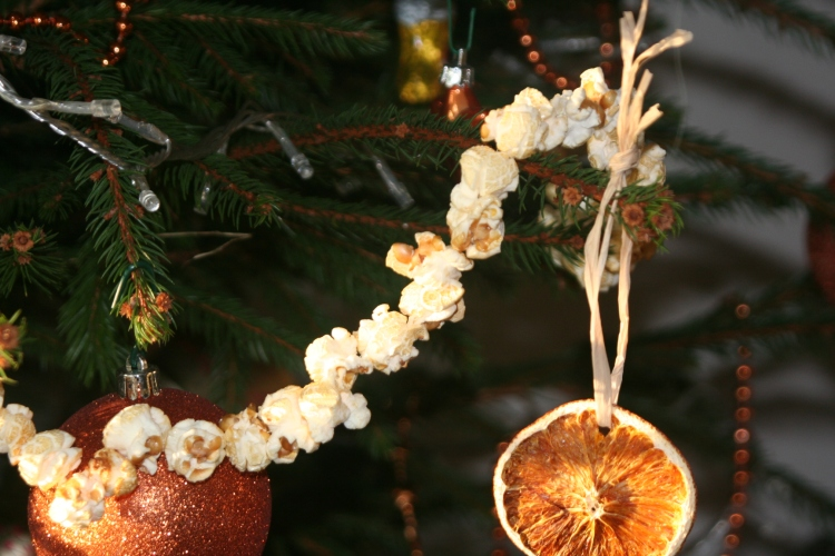 Popcorn tinsel and baked orange slices, tied with a coarse ribbon and hung from a Christmas tree; to many people, homemade decorations are better than store-bought. (Ladybird Cottage)