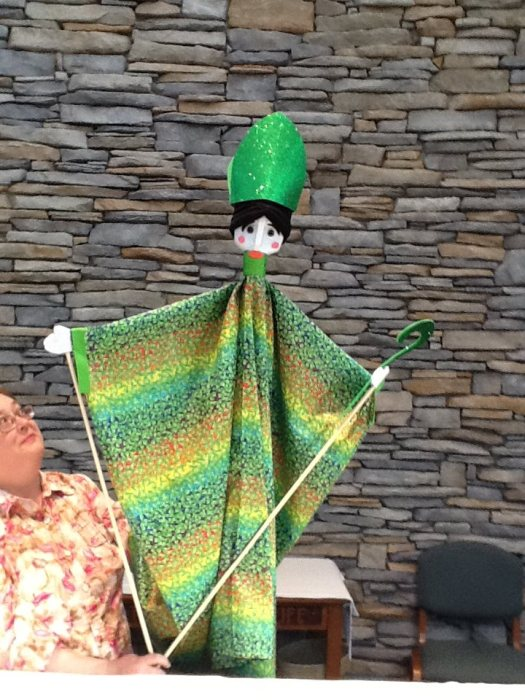 The Rev. Cricket Park, formerly of St. Patrick's, Dublin, Ohio, holding up a St. Patrick's puppet she made years ago for teaching children and entertaining at the town parade.