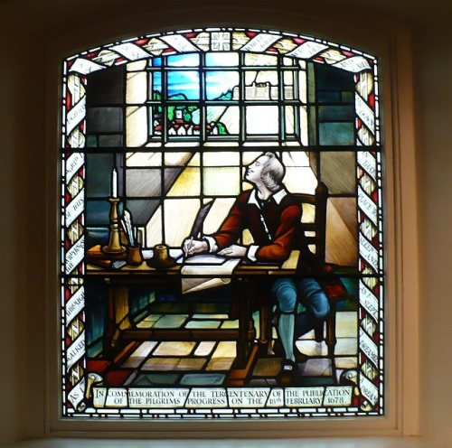 "A window of John Bunyan, depicting him during his long imprisonment for non-conformity in Bedford jail, where he began his masterpiece ""The Pilgrim's Progress."" A man becomes convinced of his sinfulness in the worldly city, and decides that he must go to the heavenly city to find forgiveness, though there are many obstacles and temptations along the way. Later his wife and children, who refused to accompany him the first time, decide that they too must flee temptation. The book greatly influenced the first white settlers of New England. (Robin Drayton/geograph.org.uk)"