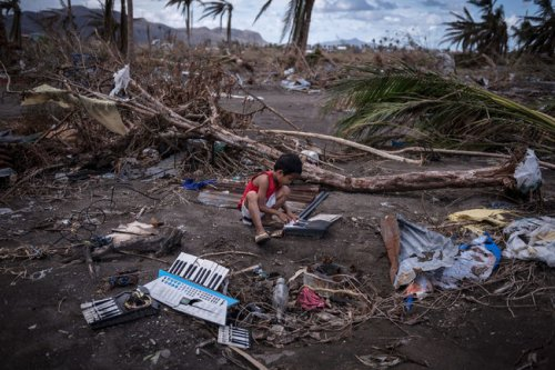 A boy playing with a broken piano last week in Tacloban. (Sergey Pomonarev/The New York Times)