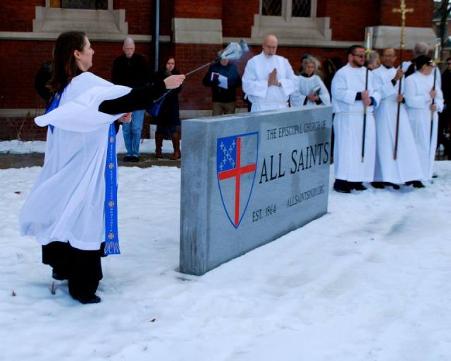 All Saints', Indianapolis, dedicated its new sign last Sunday in the snow. The Rev. E. Suzanne Wille is the rector surrounding it with prayers. (via Facebook)