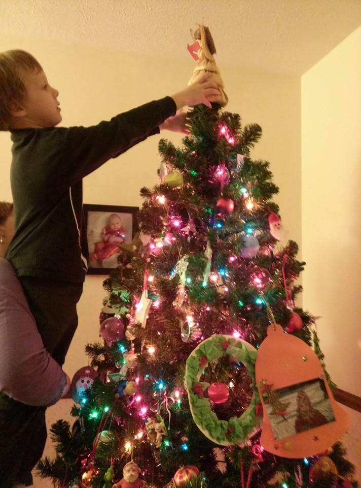 One of our favorite moms holds up her son to top off the Christmas tree. Episcopal churches don't decorate for the holyday until 24 December, but homes with children rightly do. (Facebook)