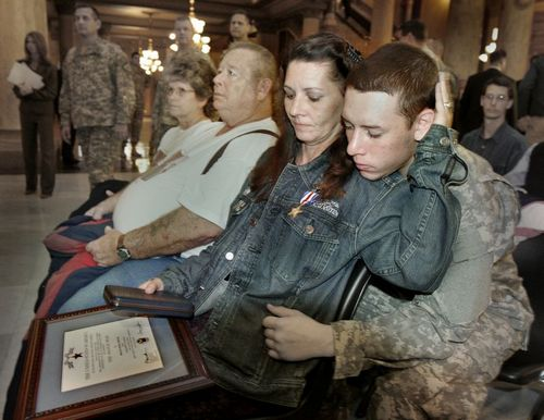 A few weeks before Christmas 2006, Sgt. Joseph Proctor of the U.S. Army was killed in Iraq after a firefight in which he gave his life to save his unit from a truck bomb. That December he was awarded the Silver Star for heroism, at a ceremony at the Indiana State Capitol. Above, his wife Beth and his son Joseph Jr., with other family members. Outwardly he seemed an ordinary man, until the moment when he laid down his life for his friends. (The Indianapolis Star)
