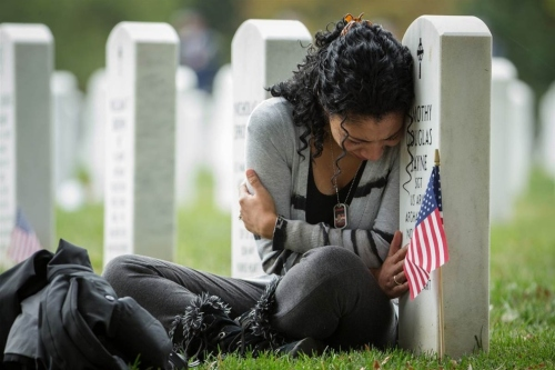 Sgt. Timothy Douglas Sayne's widow Thania weeps at his grace in Arlington National Cemetery, Virginia. He was killed in Afghanistan in 2011. (Manuel Balce Ceneta/Associated Press)