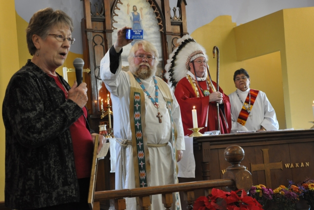 Here is the best picture you'll see all day: Wearing the feathers of a Sioux chief and not his mitre, Bishop of North Dakota Michael Smith presided over the consecration of the new St. James's, Cannon Ball, ND, last November as the Rector, John Floberg, showed a blue box from the United Thank Offering, a national fundraising mechanism for missions instituted by Julia Chester Emery, who for 40 years presided over the Woman's Auxiliary (now Episcopal Church Women) of the Domestic and Foreign Missionary Society, the formal name of The Episcopal Church. St. James's lost its previous building to a teenage arsonist three years earlier, but those blue boxes full of thanksgiving coins helped rebuild it better than ever. At left, Pat Fearing, the local UTO representative, told the story of how Ms. Emery's blue boxes work. (Photo and reporting by Mary Frances Schjonberg/Episcopal News Service)