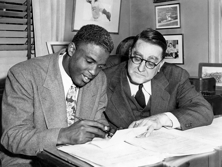Jackie Robinson signing with Branch Rickey of the Brooklyn Dodgers; Robinson made his debut in 1947 and was elected to the Baseball Hall of Fame in Cooperstown in 1962, having changed America forever. (Meyer Liebowitz/The New York Times)