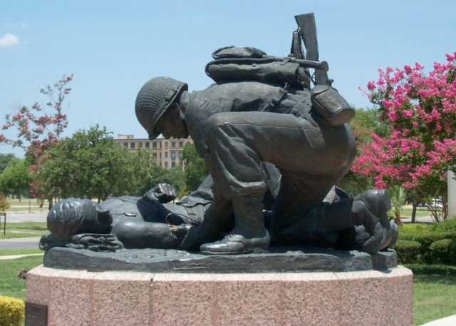 U.S. Army Combat Medic Memorial at Fort Sam Houston, San Antonio, Texas: tending to the wounded with a rifle and a load on his back.