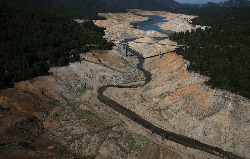 Lake Oroville, California a few days ago; the western USA is experiencing an epic drought. In normal years these brown rocks are covered with blue water. The Washington Post reports that scientists estimate the loss of water runs to 63,000,000,000,000 (trillion) gallons. (Justin Sullivan/Getty Images)