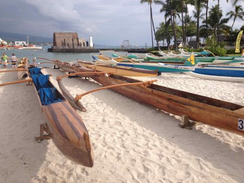 Traditional outriggers lined up on the beach on the Big Island of Hawai'i next to today's high-tech craft for this weekend's Queen Liliuokalani Long Distance Canoe Race, including a celebration of Native Polynesian culture, food and storytelling. (Queen's Race page on Facebook via Deacon Leilani)