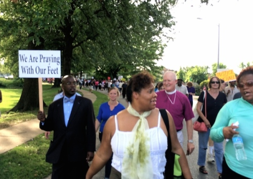 Wayne Smith, the Bishop of Missouri in the purple shirt, marched with clergy and townspeople Thursday night in Ferguson, Missouri, protesting the death of Mike Brown. The crowd and the police were mutually respectful, then yesterday more recriminations, but no violence, broke out. (Mike Angell)