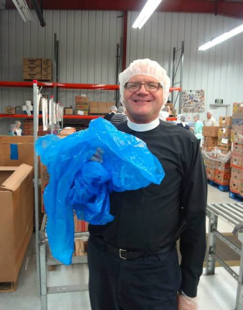 The Reverend Father Peter Bunder in all the dignity and vesture of his office, at Food Finders last Sunday. When they were done packing food for the hungry, they celebrated Mass right there on the warehouse floor. (Chapel of the Good Shepherd on Facebook)