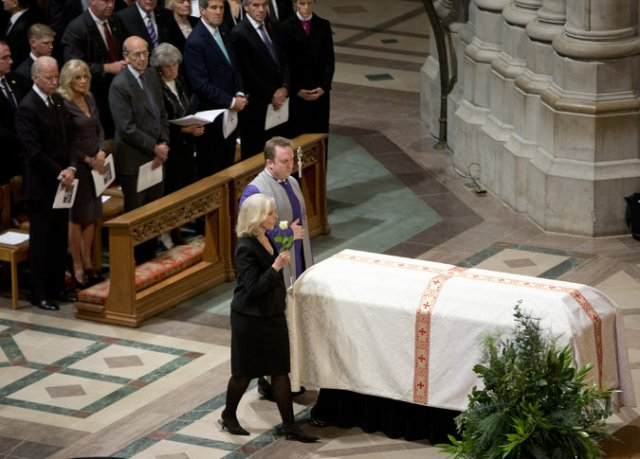 """The funeral of the late Washington Post editor Ben Bradlee was held Wednesday at Washington National Cathedral; his widow Sally Quinn is seen above, escorted by the verger. An upper class Bostonian and World War II veteran whose speech was both """"high church"""" and profane, Bradlee and his reporters helped save American democracy from a criminal conspiracy by President Richard M. Nixon. (Carolyn Kaster/Associated Press)"""