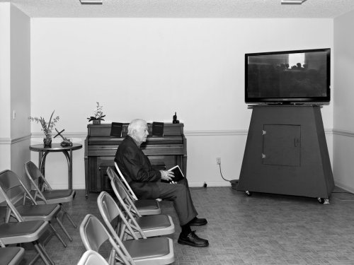 """Jimmy Carter at 80, still teaching Sunday School at Maranatha Baptist Church in Plains, Georgia, including any tourists who happen by. Acclaimed photographer Alec Soth took this shot as part of a project along the back roads of America. He and a writer-friend, Brad Zellar, told people they worked for a fictitious newspaper, shooting and writing up whatever they found along the way – and publishing the results. In time """"The Winter Garden Dispatch"""" gained a following and printed editions in six states; meanwhile much of Soth's work hangs in major institutions, including the Museum of Modern Art in New York. (Reportage: The New York Times)"""