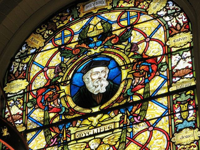 Wyclif window at Wycliffe College Chapel in Toronto; his name is spelled various ways. He was a professor of theology and philosophy at Oxford who questioned various Church doctrines; he believed strongly that laypeople should be able to read the Bible in their native language, and translated the Vulgate into English. He supported the idea of a national church without international (papal) interference, and he taught that individuals could have a direct, unmediated relationship with God. But when he publicly doubted Transubstantiation or the Real Presence of Christ in the Eucharist, he went too far for the times and was hounded out of office. (Wikipedia)