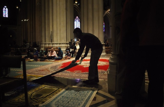 "Laying out prayer rugs: Washington National Cathedral kicked up controversy last Friday by hosting Muslim noonday prayers for a well-connected local group without a mosque, led by the South African ambassador, a friend of the cathedral clergy. They intended to promote interfaith toleration and respect, and to fulfill the cathedral's mission as the national ""house of prayer for all people,"" but others didn't see it that way. To forestall any security threats, the service was limited to invited ticket-holders, which locked out Episcopalians and other Christians so Muslims could pray to Allah in America's semi-official church. There was only one minor disruption of the service, but over the weekend a storm continued to rage on social media. Overnight on Sunday, the so-called Islamic State beheaded another kidnapped American, Peter Kassig, which had nothing to do with the Muslims in D.C. except guilt by association. Maybe next month the clergy will transform the space for Zoroastrians. (Astrid Riecken/Washington Post)"