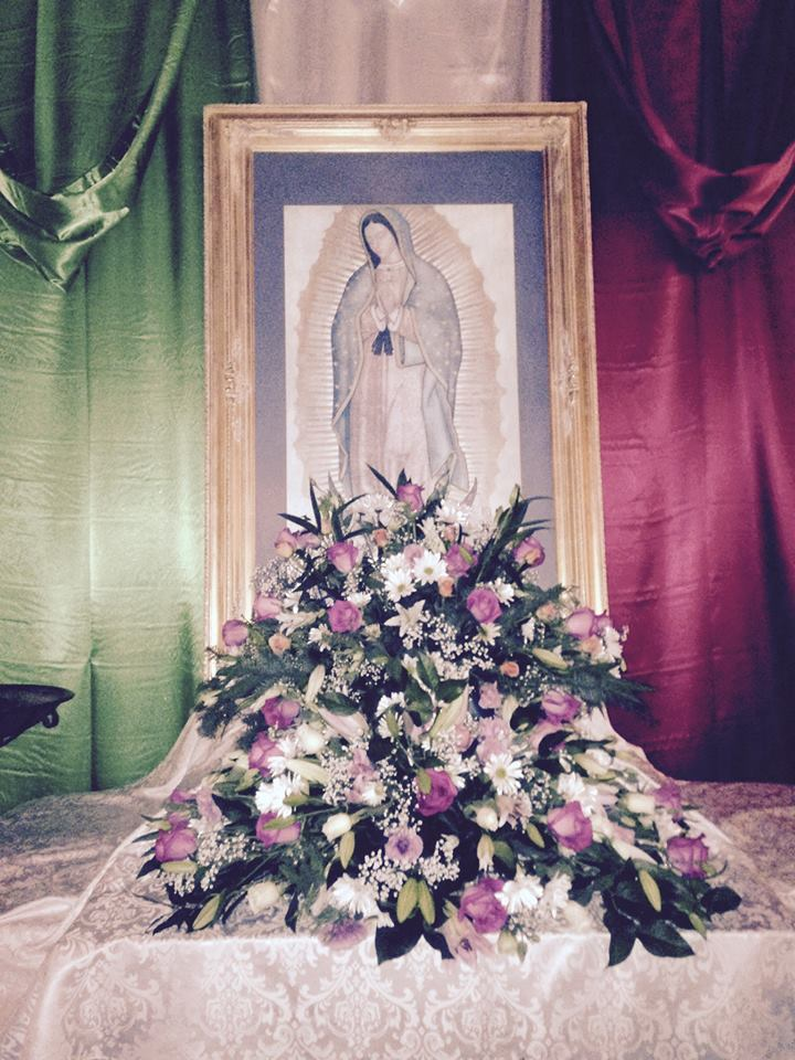 A shrine to Our Lady of Guadalupe at All Saints', Watsonville, California, illustrating the central role of roses and other flowers in the story of her apparition. She showed a local Aztec man flowers growing out of season at the top of a hill where she wanted a shrine built. He picked the flowers, put them in his cloak and carried them to his doubtful bishop. When he opened the cloak, the flowers fell out and there where they had been on the inside of the garment, was her famous image.