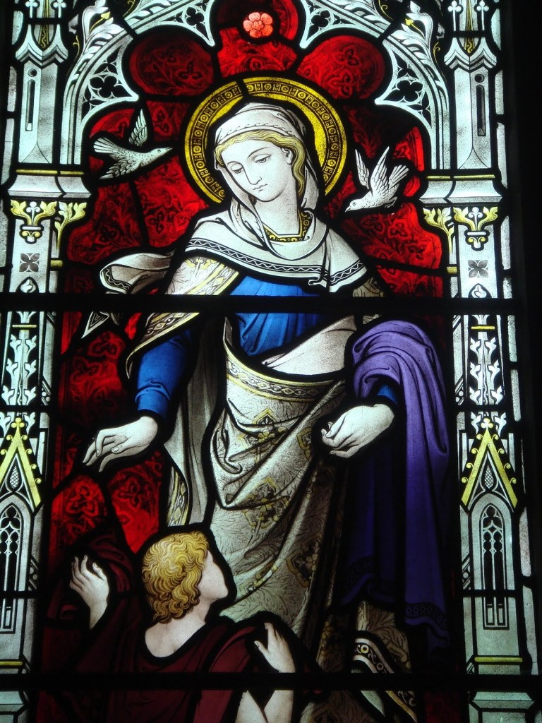 """St. Dorcas window at All Saints', Freshwater on the Isle of Wight. Known as Tabitha in Aramaic, she devoted herself to """"good works and acts of charity."""" Once when she fell ill, the church sent for St. Peter, who came and revived her (Acts 9:36-42)."""