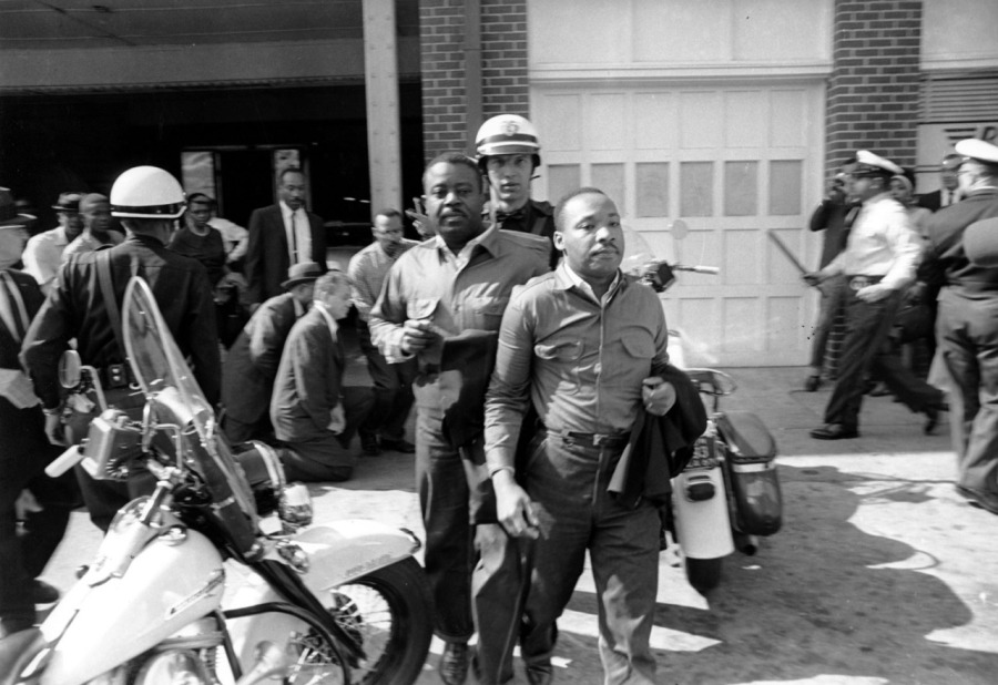 The 1963 Birmingham, Alabama campaign of the U.S. civil rights movement was a major turning point; for the first time, children were allowed to join the demonstrations, after thousands of adults had been arrested and the movement bankrupted after bailing them out of jail. Americans sat glued to video of police violence against the children, including using water cannons with so much force that local leader the Rev. Fred Shuttlesworth had to be hospitalized. A state court had declared all the protests illegal. Finally Dr. Martin Luther King Jr. and his closest associate, Dr. Ralph Abernathy, just behind King above, joined the street protests and were taken into custody; King's wife had just given birth to their fourth child, but he wasn't allowed to call home. Instead he was placed in solitary confinement, where he wrote his famous Letter from a Birmingham Jail, explaining the necessity of the movement's actions and castigating White religious leaders for their timidity, especially the Episcopal Bishop of Alabama. (Associated Press) #BlackHistoryMonth