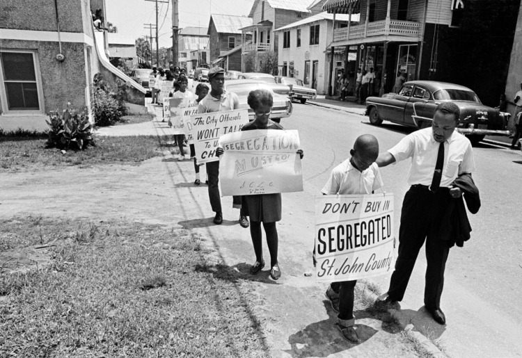 Dr. King encouraging a young marcher protesting racial segregation in housing in St. Augustine, Florida in 1964. He was arrested for organizing this peaceful demonstration, and was still in jail as Congress neared a climactic vote on the groundbreaking Civil Rights Bill after an epic 57-day filibuster. It finally passed, with a greater percentage of Republican votes than Democratic ones. (Associated Press)