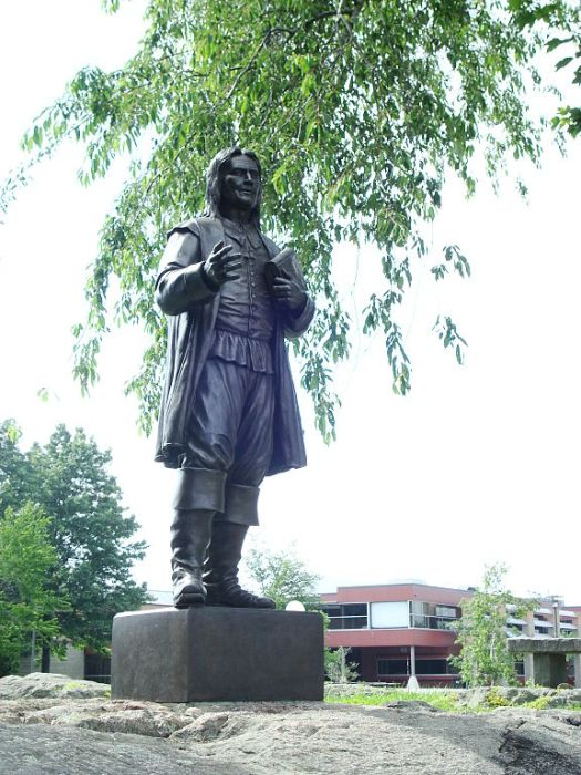 "A statue of Roger Williams at the university named for him in Bristol, Rhode Island, founded in 1956 (and religiously unaffiliated). Williams the man was persecuted by Anglican Archbishop William Laud for Nonconformist views, and left England in 1630. He arrived in Massachusetts, but after objecting to the right of Laud's enemies the Puritans to prosecute their version of religious violators, he moved south, established a colony in Rhode Island, and advocated famously for a ""wall of separation"" between church and state. Anglican or Puritan, he didn't want the government telling him what to think. (Wikipedia)"