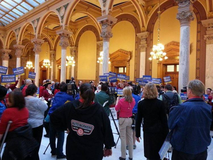 A rally last week at the Indiana Statehouse against a bill creating a religious exemption to local anti-discrimination ordinances, allowing businesses to refuse to serve LGBTs. The bill, trumpeted to protect those who disapprove of same-sex marriage, doesn't limit the type of business or specify what kinds of customers can be turned away; critics say anyone could be a target. It passed yesterday, with all but five Republicans voting for it. Nineteen states already have similar laws. (John Steele)