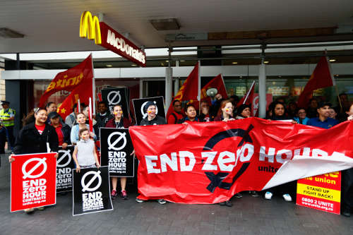 """McDonald's workers picketing a location in Auckland Friday, part of an international movement to raise wages for fast-food workers. A unique grievance in New Zealand is management's demand that workers be available full-time, whether they're on duty or not. Stores in other countries don't get away with that; if you want a person's time, you have to pay for the privilege, for """"the worker deserves her wages."""" (Henry Ackland/Radio New Zealand)"""