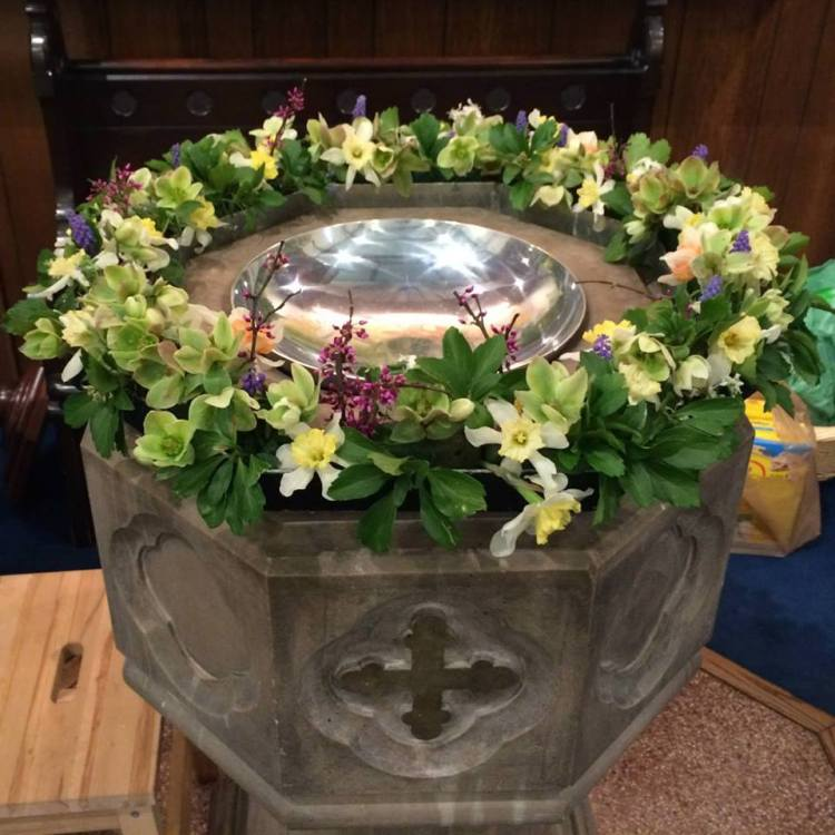 Baptismal font at St. John's, Lafayette, Indiana, with a child's step stool in the lower left. (parish photo)