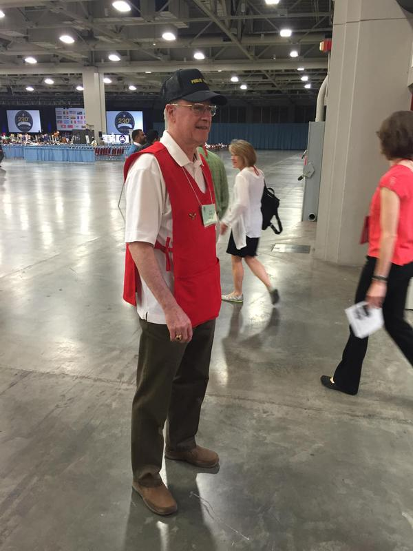 What do the spouses of Episcopal bishops do during the 9-day General Convention? Larry Waynick, husband of the Bishop of Indianapolis, is a volunteer host in a $2 red smock, starting at 6 in the morning. Too bad he doesn't know anybody who could pull some strings. (The Rev. Canon Bruce Gray)