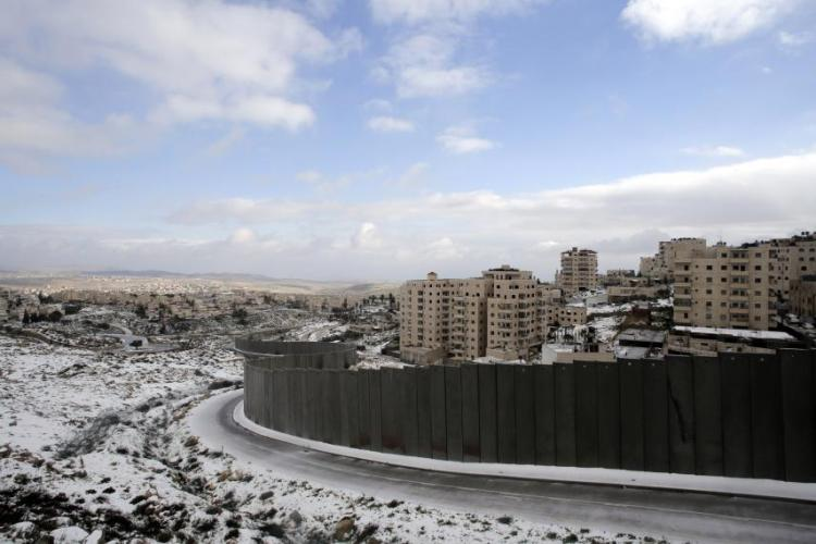 A wall runs hundreds of miles through the Occupied Territories in the West Bank, separating apartment buildings for Israeli settlers from the Shuafat refugee camp near Jerusalem, above. The wall is unfinished, but Bethlehem and its holy sites are surrounded. (Ammar Award/Reuters)