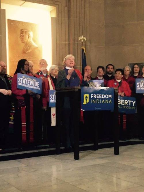 "The Episcopal Bishop of Indianapolis, the Rt. Rev. Cate Waynick, addressed the Freedom Indiana rally at the Statehouse yesterday, hoping to stop a ""super-RFRA"" bill that would legalize anti-Gay discrimination by small businesses throughout the state. RFRA stands for Religious Freedom Restoration Act, a version of which was passed last year and plunged the state into threats of financial boycotts and a media frenzy. Lost convention business cost Indiana at least $60 million, according to one study. A little while after the rally above, the bill was killed by the committee chairman, despite a Republican ""supermajority"" in the legislature. (John Steele)"