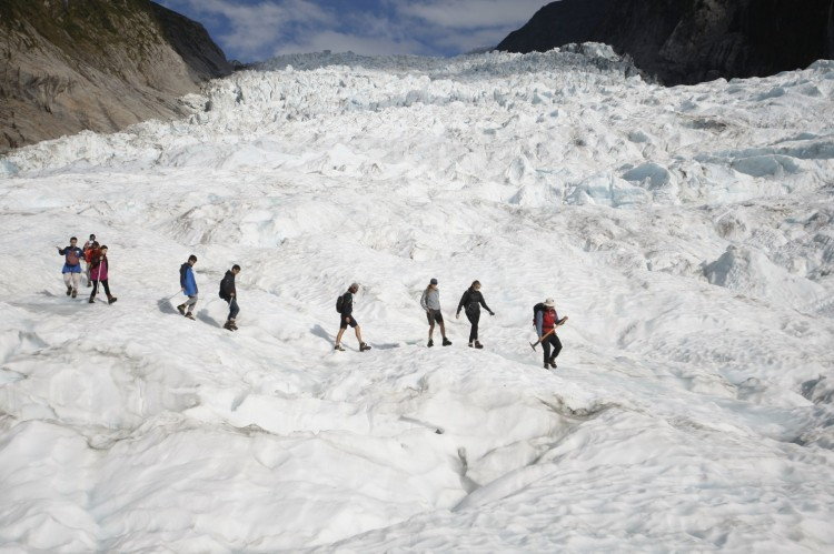 New Zealand's Fox Glacier, like others, is melting rapidly – but unlike most, people feel its loss of mass directly. It has long served recreational tourists in a national park on the South Island, flowing down between mountain peaks to a temperate rain forest in the valley below; people used to be able to walk right up. But the ice has receded so much that now the only way to get to it is by helicopter, with hikers limited to 80,000 a year. Since the turn of the last century, the Fox and Franz Josef Glaciers have both retreated about 3 kilometers, leaving the exposed mountains subject to dangerous rock slides. But the mass of humanity continues burning fossil fuels without repentance. (Nick Perry/Associated Press)