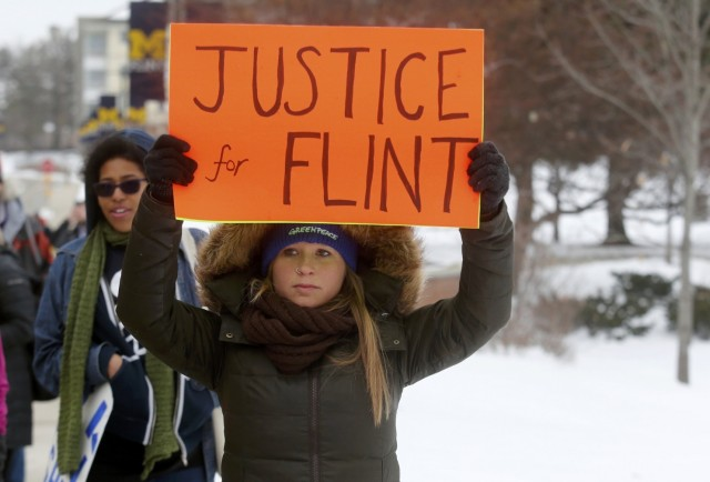 """A demonstration two weeks ago in Flint, Michigan, where the entire population has been poisoned by lead in the water, and where a shocking outbreak of Legionnaire's disease (87 cases, 9 deaths) has never been thoroughly investigated, because the state refused to allow the Centers for Disease Control to come in. """"O God of vengeance, show yourself."""" (Rebecca Cook/Reuters)"""