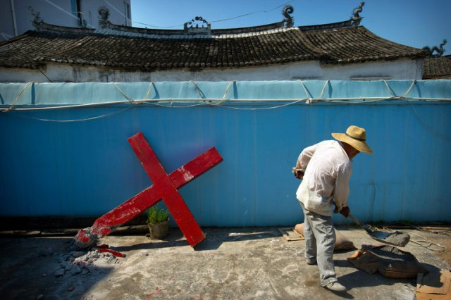 China has about 60 million Christians, less than 5% of the population, who worship in churches recognized by the government as well as underground or house churches. Nevertheless, the government has cracked down hard on public displays of the cross, forcibly removing an estimated 1200 to 1700 from the tops and sides of church buildings in Zhejiang Province since 2015, with more to come in its ongoing campaign of intimidation. Acts of defiance, including barricading the gates so the bulldozers can't get in, have been crushed. (Mark Schiefelbein/Associated Press)
