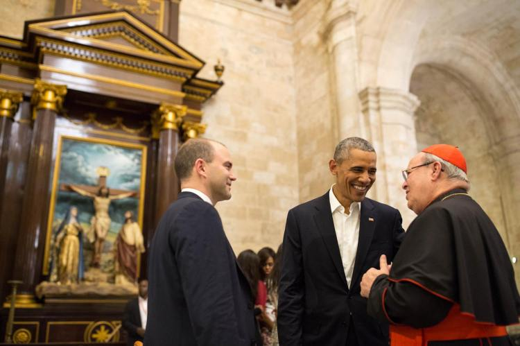 Every now and then, peace breaks out: the Archbishop of Havana, Cardinal Jamie Ortega, has announced his retirement a few weeks after his great triumph, helping to negotiate normalized relations between Cuba and the USA, and welcoming President Obama to his Cathedral of the Virgin Mary of the Immaculate Conception. Above: with the President and Ben Rhodes, deputy national security adviser; Michelle Obama is visible behind them. (Pete Souza/The White House)
