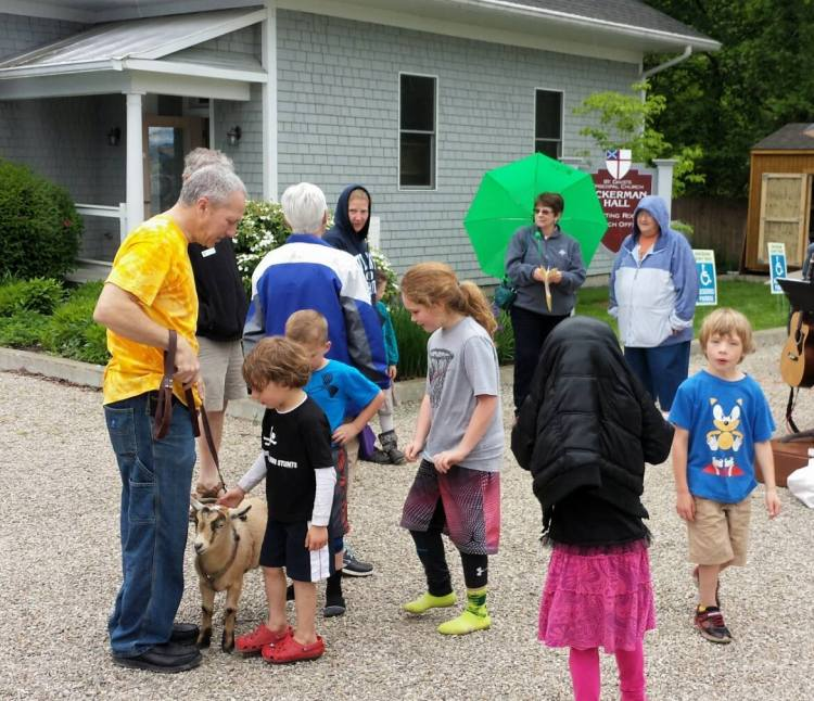 A kid for the kids: the Brown County, Indiana Farmers' Market at St. David's, Bean Blossom, dedicated its children's play area last weekend, with a baby goat as one of the guests of honour. (Marylin Day)
