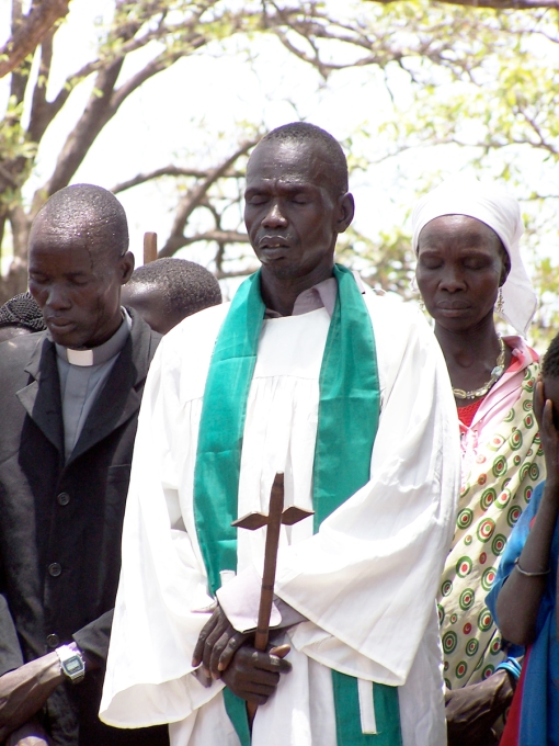 An Episcopal priest in South Sudan giving a public prayer. Today was chosen to commemorate the martyrs because on May 16, 1983, Anglican and Roman Catholic clergy in Sudan signed a declaration that they would not abandon Christ even under threat of Shariah law. Persecutions increased in the next several years, including the murder of clergy and lay leaders; the burning of churches, hospitals, schools and Christian villages; and bombings at Sunday services. Mostly-Muslim Sudan and mostly-Christian South Sudan separated as a result of a plebiscite and subsequent treaty in 2011; civil war has continued in the South as tribes and political factions fight for control of oil and other resources. (David Copley)