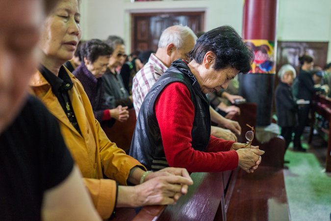 Worshipers at an unidentified, probably Roman Catholic, church in Wenzhou, China, probably at a Roman Catholic church. China has 60 million Christians, most of whom keep their heads down to avoid running afoul of the government. (Sim Chi Yin/The New York Times)