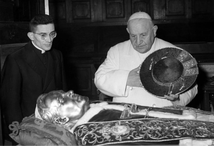 Cardinal Loris Francesco Capovilla died last week, Pope John XXIII's personal secretary and spiritual son. He helped guide the preparations for Vatican Council II, the lengthy conclave at which Roman bishops agreed to reform the liturgy, including permitting the use of common languages understood by worshipers. Father Capovilla was a poor boy, always destined for the Church, who attended a seminary high school, and became a priest in Venice in 1940. He was a military chaplain during World War II and later became a journalist and religious broadcaster. He met Cardinal Angelo Roncalli, the future pope, when he was installed as Archbishop of Venice in 1950; they developed an instant rapport. When Roncalli was elected pope at age 77 in 1958, he took Capovilla with him. Capovilla was credited with providing wise counsel and public relations management in the run-up to Vatican II; the conservative hierarchy was fearful of public debate that might lead to change and a loss of control, but John XXIII won the support of the faithful by his humility and open affection. The council lasted two years and succeeded in modernizing worship; the Liturgical Movement affected Anglicanism deeply as well, including Prayer Book Revision in the United States. After the Pope's death Capovilla devoted his life to John's memory and legacy, publishing his diaries, even moving to the late Pope's birthplace and helping to run a museum dedicated to his life. Successive popes heaped honors on the former secretary, but he retained his humility and love for his mentor for the rest of his life. Above: paying their respects to the body of Pius XII, whose face is covered with a silver mask, shortly after his death. (Luigi Felici/Associated Press)