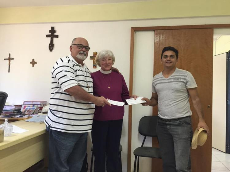 Bishop Cate Waynick of Indianapolis, our Episcopal Visitor, presented a check for $13,000 yesterday (including a small sum from us) to Bishop Mauricio Andrade of the Diocese of Brasilia, and Luciano Sousa Neves, to help expand the after-school program in Brasilia's inner city. We are glad for the chance to help; thank you, Daily Office donors. (The Rev. Jeffrey Bower, World Missions Committee of the Diocese of Indianapolis)