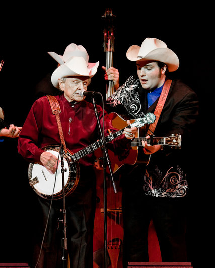 """The great folksinger and banjo picker Ralph Stanley has died, after a lifetime of professional renown but not fame. He's most commonly identified with bluegrass music, but he disdained the term and just sang in the Primitive Baptist style he grew up with in the mountains of Virginia. His music was featured prominently in the film """"Brother, Where Art Thou?"""" Above, with his grandson Nathan at a performance in 2012. (Chad Batka/The New York Times)"""