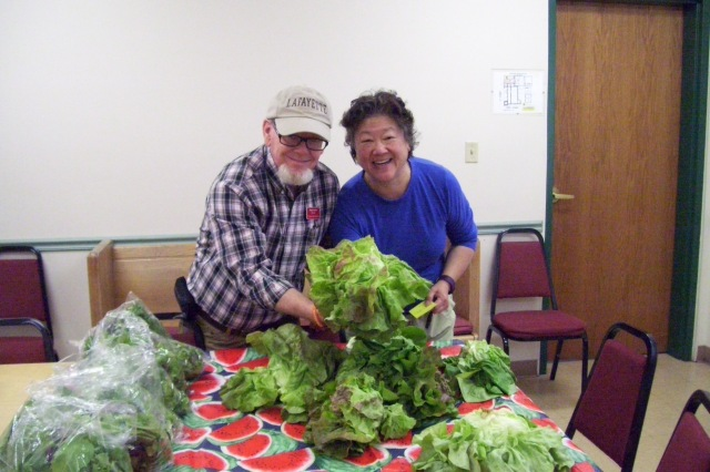 Steve Starks, director of the St. John's/LUM Food Pantry in Lafayette, Indiana, arranging lettuces with Pauline Shen, who coordinates produce donations from the nearby Farmers' Market. What the farmers don't sell, she distributes to several feeding programs in town, including this one in my home parish. (Josh Thomas/The Daily Office)